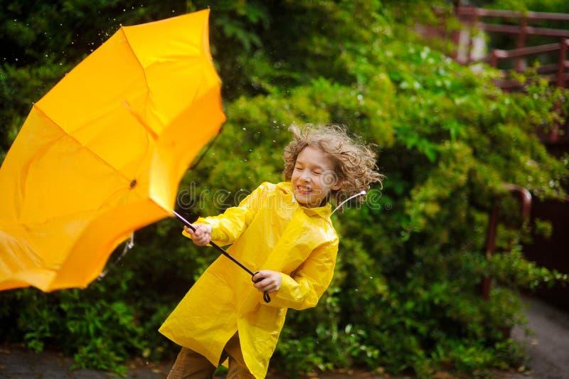 Der Junge in einem hellen gelben Regenmantel mit Bemühung hält einen Regenschirm vom Wind lizenzfreie stockbilder