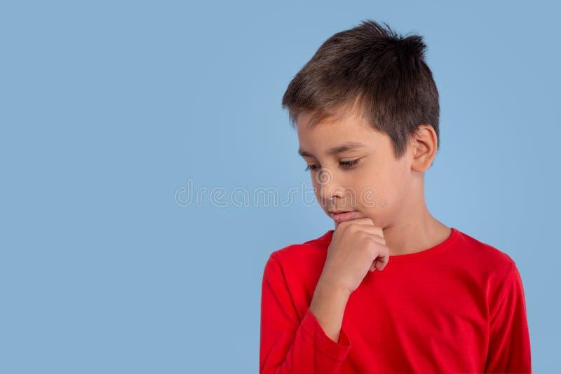Der Junge, der in einem roten T-Shirt gekleidet wird, denkt an, was das, er d schaut lizenzfreie stockfotos