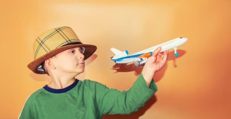 Der Junge in einem Strohhut hält ein Passagierflugzeug, das Konzept der Freiheit und Reise lizenzfreies stockbild