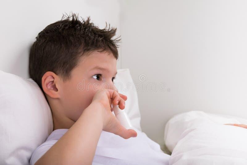 Der Junge in einem weißen Bett hält in seiner Hand eine Phiole Medizin für die Nase, betrachtet den Platz stockbilder