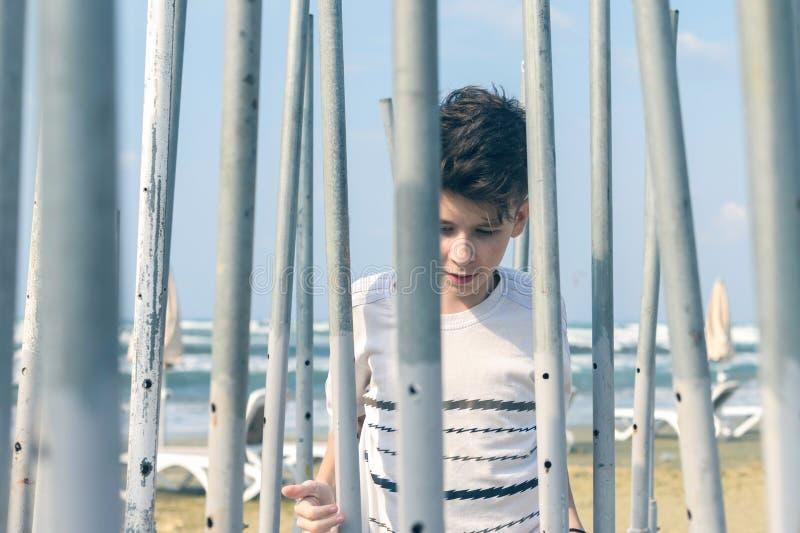 Der Junge, der, einen Ausweg des Labyrinths der Eisenrohre zu finden spielt und versucht lizenzfreies stockfoto