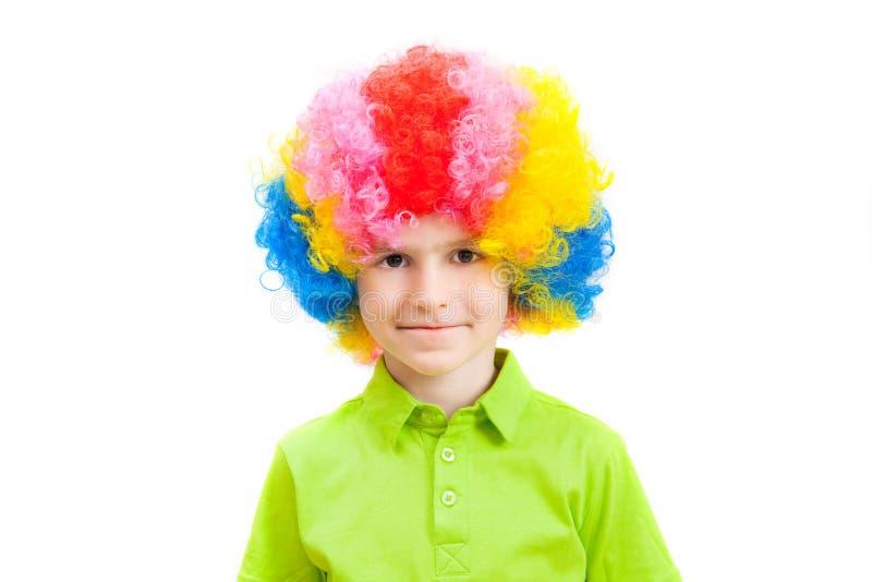 Der Junge in einer mehrfarbigen Clownperücke stockfotos