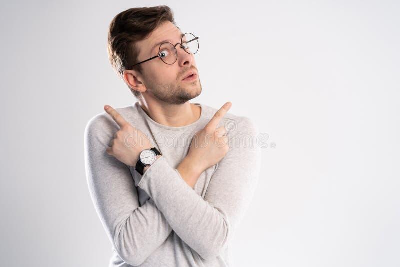 Der junge emotionale unvorsichtige Mann, der auf weißem Hintergrund mit Kopienraum für Text lokalisiert wurde, setzte seinen Kopf stockfotos