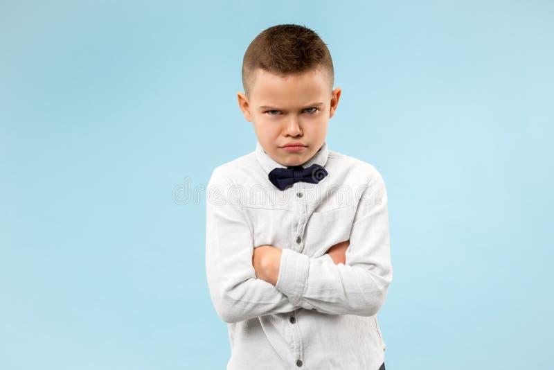 Der junge emotionale verärgerte jugendlich Junge auf blauem Studiohintergrund stockbild