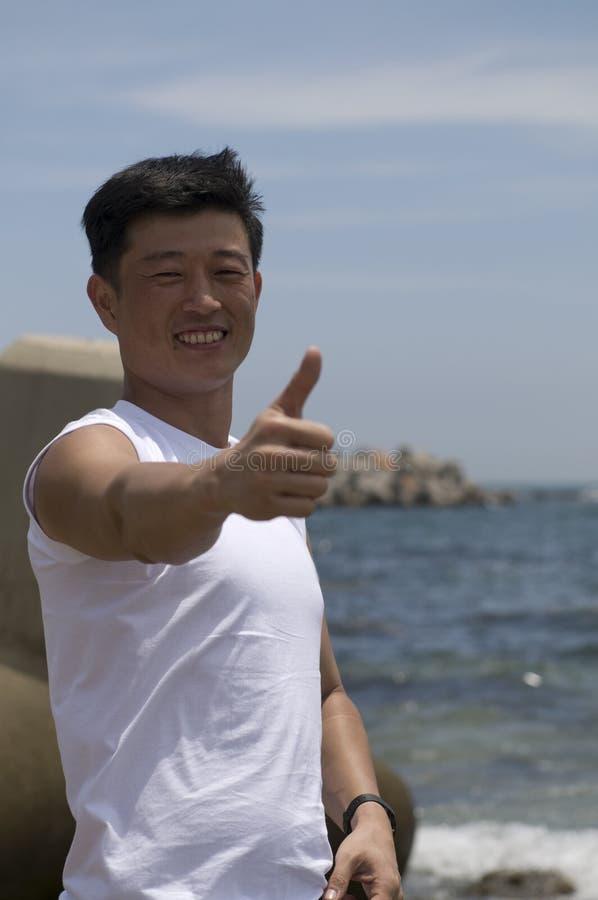 Der junge erfolgreiche Mann auf dem Seestrand und dem s lizenzfreie stockbilder