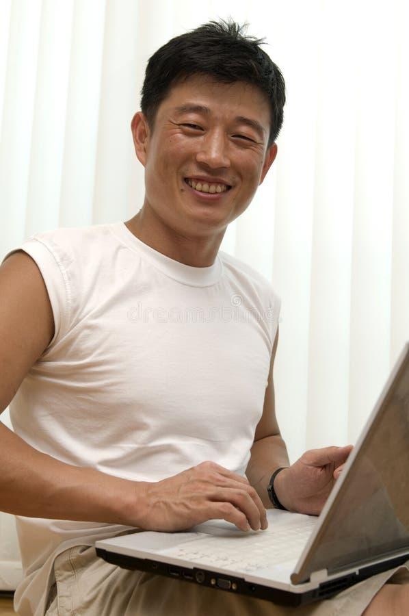 Der junge erfolgreiche Mann mit dem Computer sitzt lizenzfreie stockfotografie