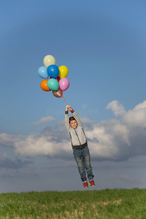 Der Junge fliegt weg in Ballone lizenzfreie stockfotos