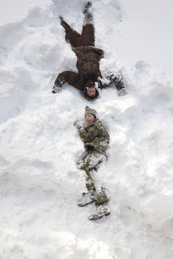 Der Junge gelegt auf den Schnee lizenzfreie stockfotografie