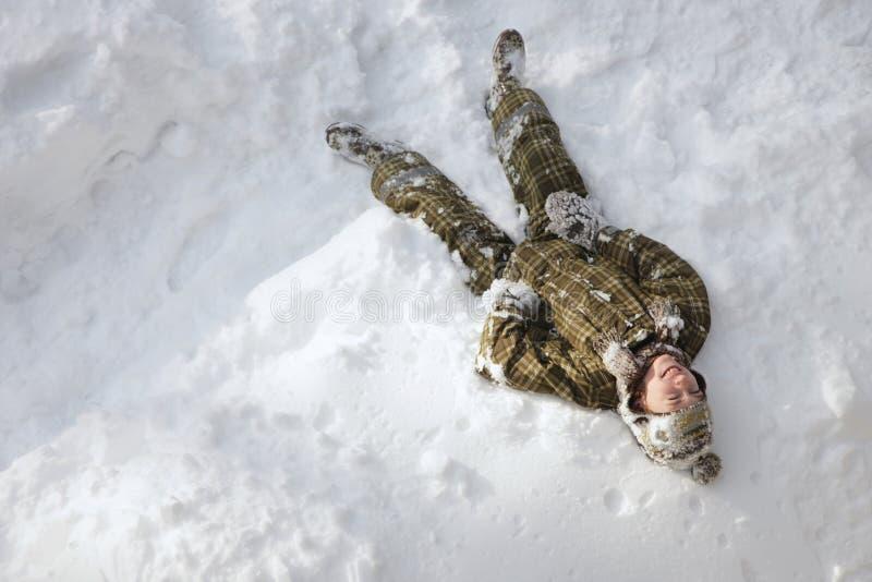 Der Junge gelegt auf den Schnee lizenzfreie stockfotos