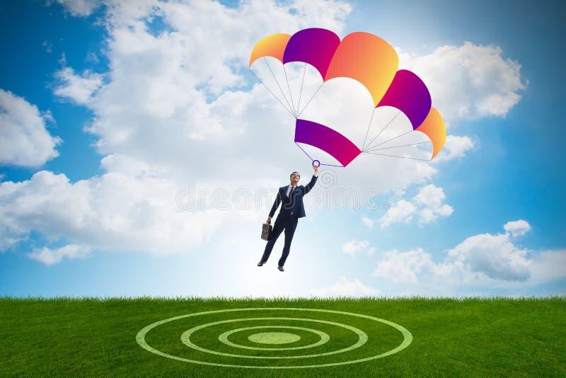 Der junge Geschäftsmann, der auf Fallschirm im Geschäftskonzept fällt stockfoto