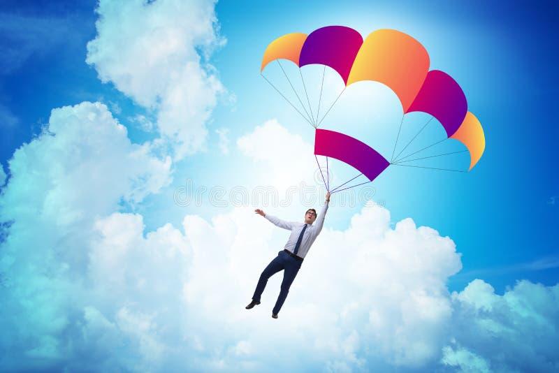 Der junge Geschäftsmann, der auf Fallschirm im Geschäftskonzept fällt stockbilder