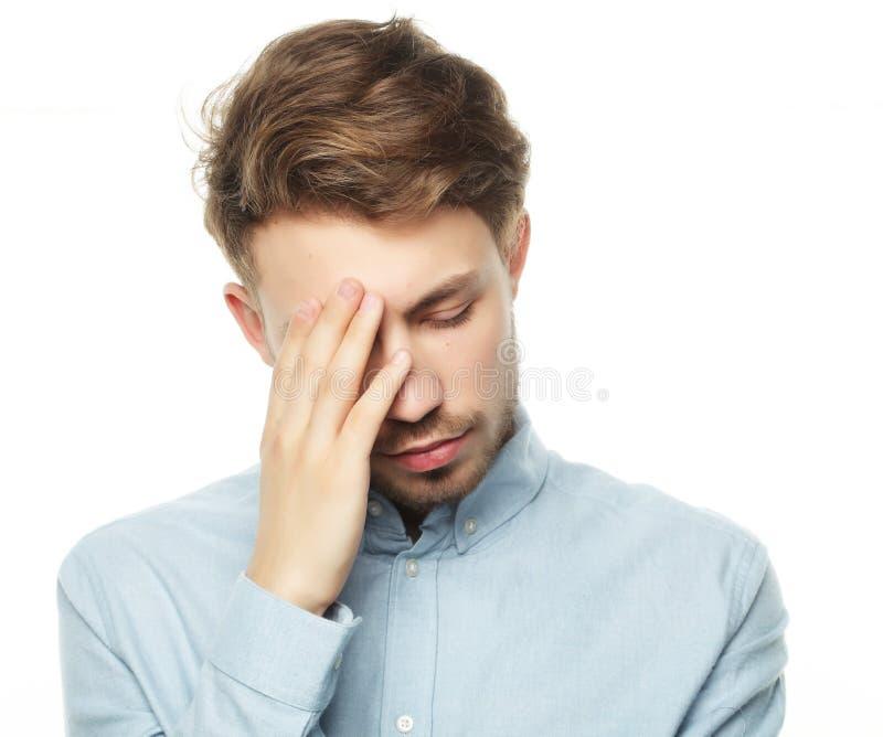 Der junge Geschäftsmann, der seinen Kopf berührt und Augen hält, schloss lizenzfreie stockfotos
