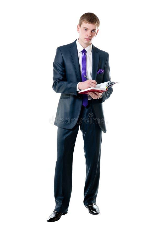 Der junge Geschäftsmann in einer Klage mit täglichem Protokoll stockbild