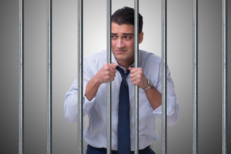 Der junge Geschäftsmann hinter den Stangen im Gefängnis stockbild