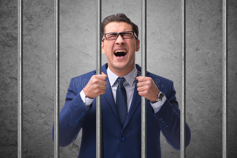 Der junge Geschäftsmann hinter den Stangen im Gefängnis lizenzfreie stockfotos