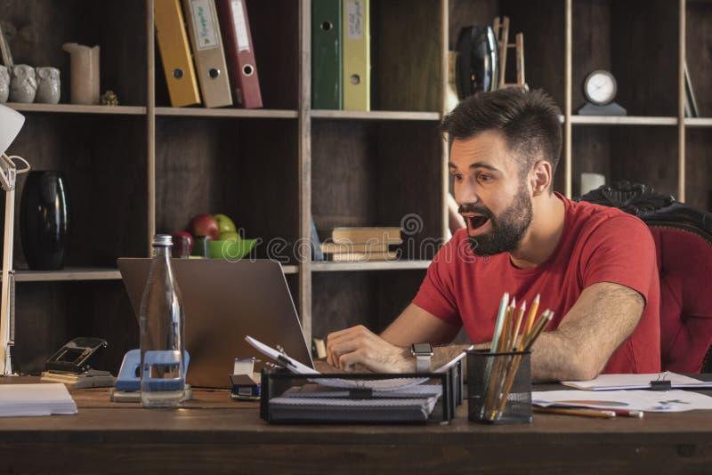 Der junge Geschäftsmann, der hinter Schreibtisch sitzt und sehen kühle Nachrichten auf Laptop lizenzfreie stockbilder