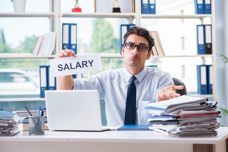 Der junge Geschäftsmann, der um Lohnerhöhung im Büro bittet stockfotografie