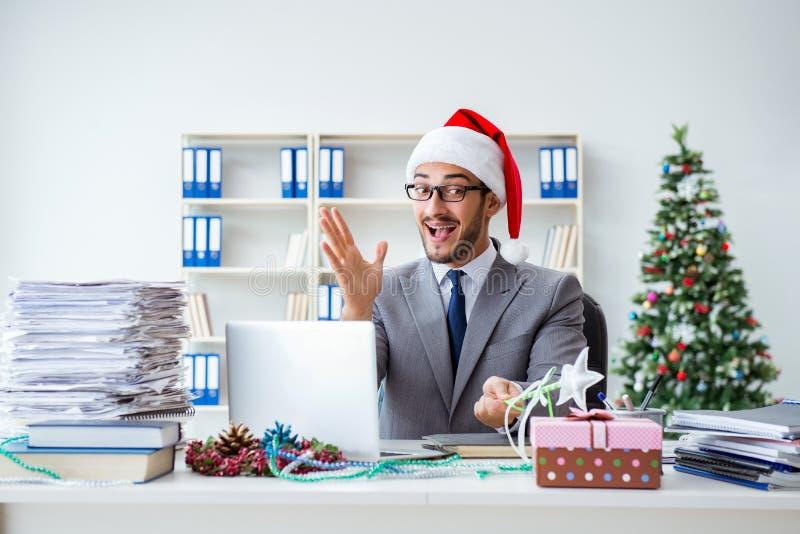 Der junge Geschäftsmann, der Weihnachten im Büro feiert stockfoto
