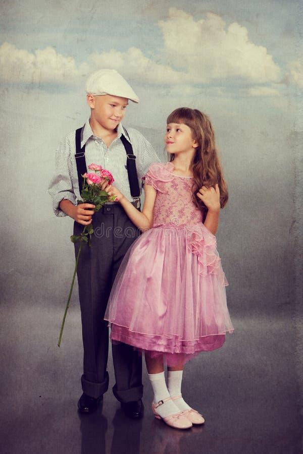 Der Junge gibt dem Mädchen eine Blume stockfoto