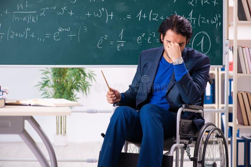 Der junge gut aussehende Mann im Rollstuhl vor Tafel lizenzfreie stockbilder