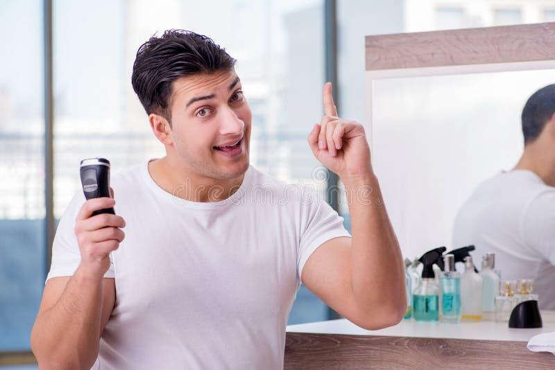 Der junge gutaussehende Mann, der sich morgens rasiert lizenzfreie stockfotos