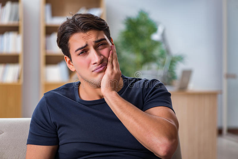 Der junge gutaussehende Mann, der unter den Schmerz leidet lizenzfreie stockfotos