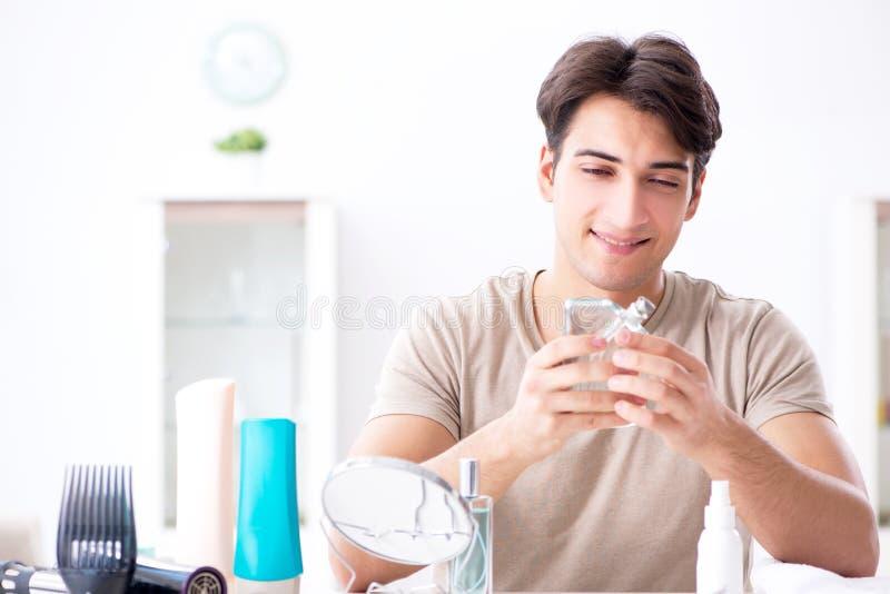 Der junge gutaussehende Mann, der im Spiegel anstarrt stockfoto