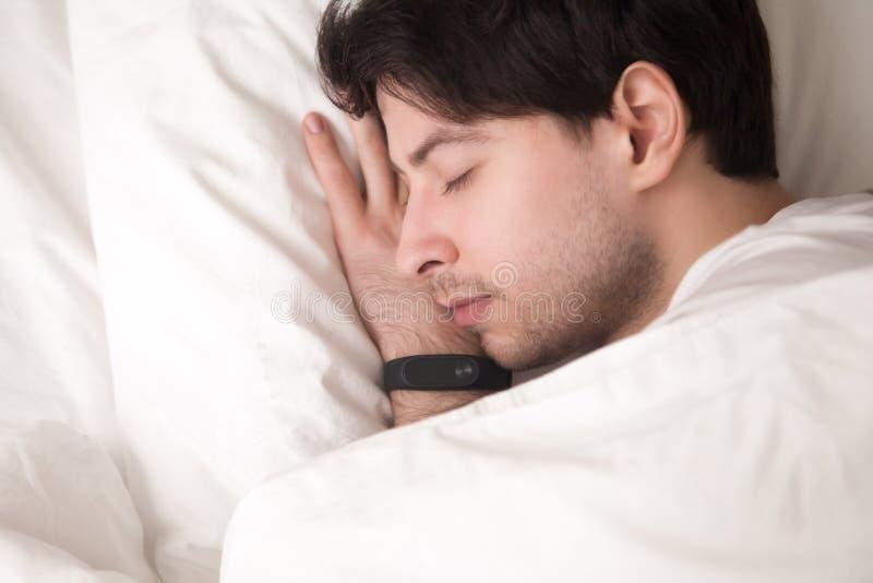Der junge gutaussehende Mann ist schlafend und die Manschette, der seins Schlaf aufspürt lizenzfreies stockbild
