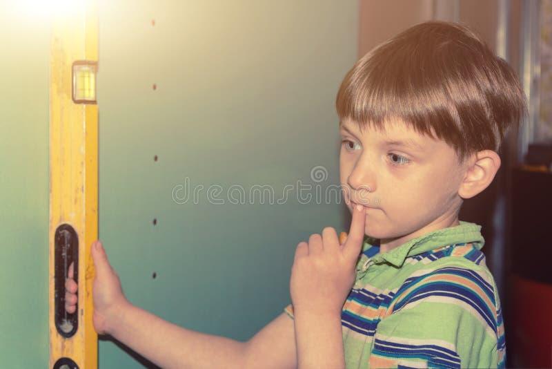 Der Junge hält das Bauniveau und überprüft die Genauigkeit der Wand und dachte an die Reparatur lizenzfreies stockfoto