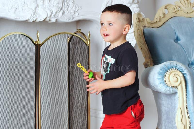 Der Junge hält ein Spielzeug in seiner Hand stockbilder