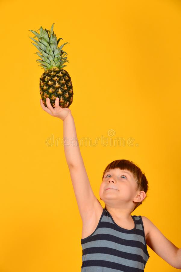 Der Junge hält eine Ananas über seinem Kopf, auf einer ausgestreckten Hand auf einem gelben Hintergrund lizenzfreies stockfoto