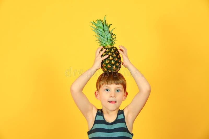 Der Junge hält eine Ananas auf seinem Kopf, auf einem gelben Hintergrund stockbild