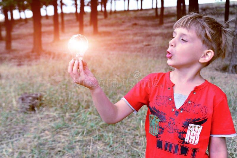Der Junge hält eine Glühlampebirne, die in seiner Hand brennt und sie mit Überraschung und Bewunderung betrachtet lizenzfreies stockfoto