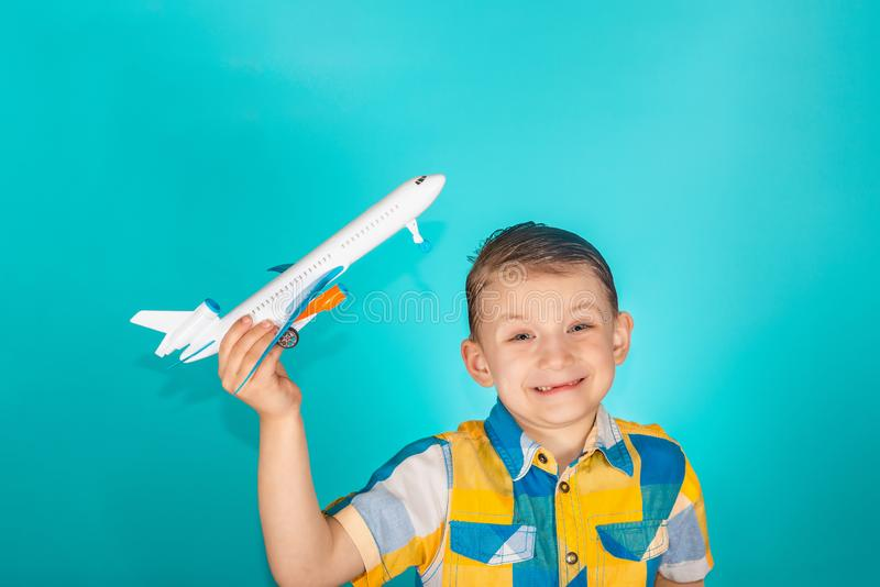 Der Junge hält eine Spielzeugfläche in seiner Hand und in Lächeln in einem hellen Farbhemd, Foto im Studio auf einem blauen Hinte stockfotografie