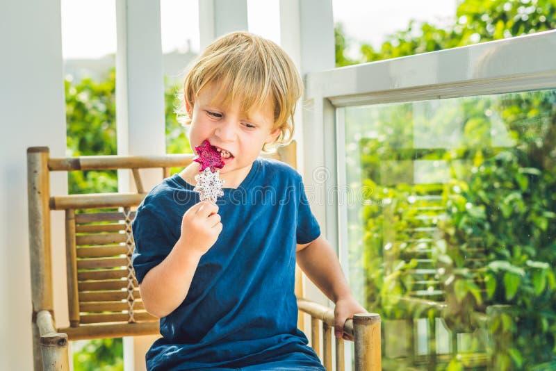 Der Junge hält Smoothies von einer Drachefrucht mit einem tadellosen Blatt und einem Trinkhalm lizenzfreies stockbild