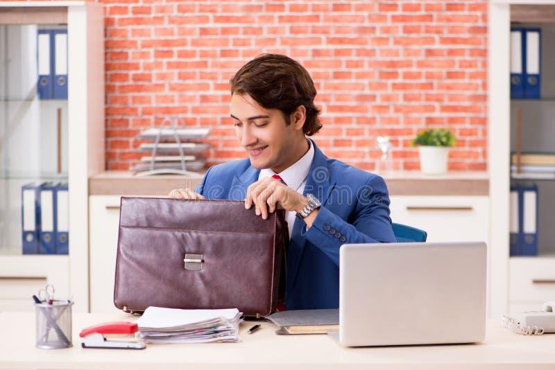 Der junge hübsche Angestellte, der im Büro arbeitet stockbild