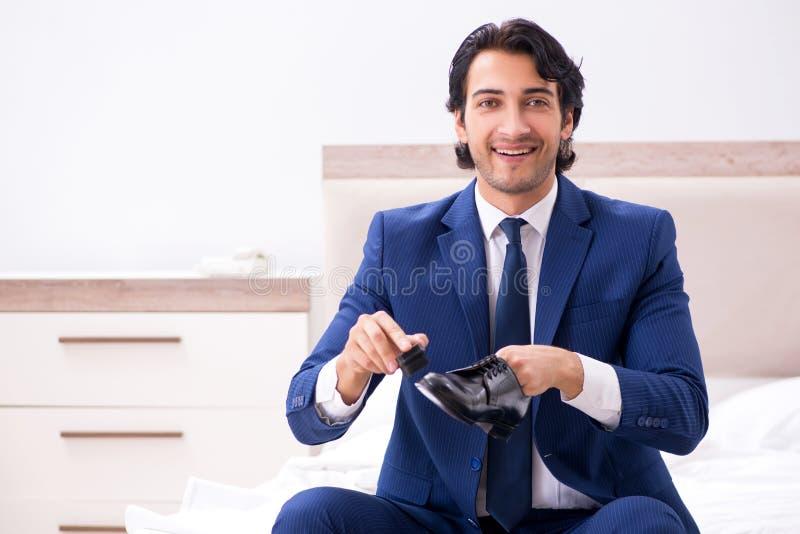 Der junge hübsche Geschäftsmann, der zu Hause Schuhe wählt stockbilder