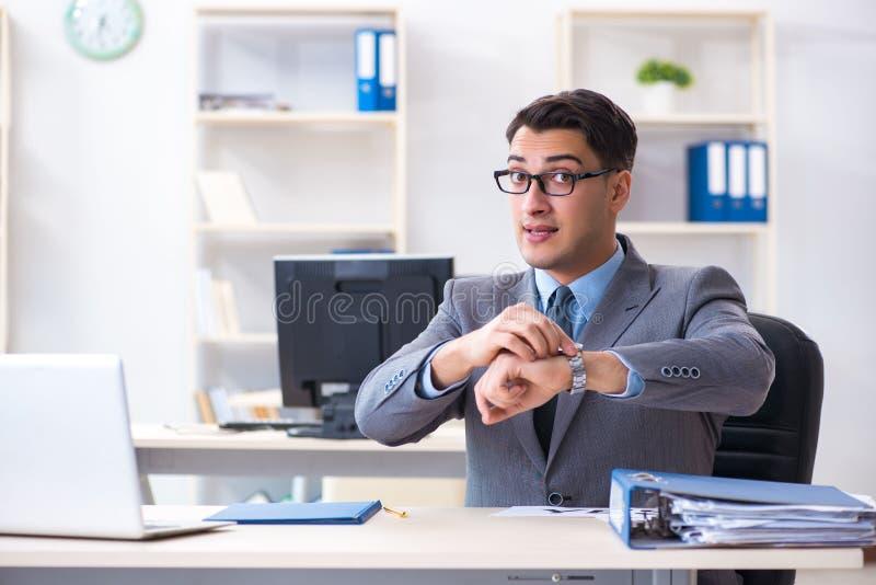 Der junge hübsche Geschäftsmannangestellte, der im Büro am Schreibtisch arbeitet stockbilder