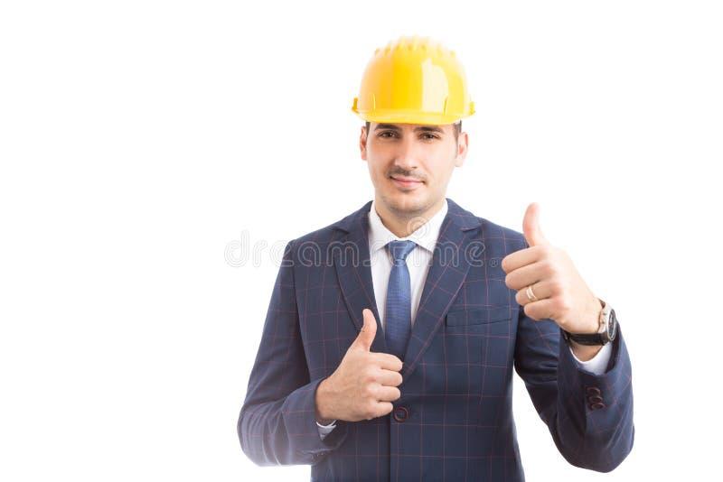 Der junge hübsche Ingenieur, der Daumen herstellt, up Geste stockfoto