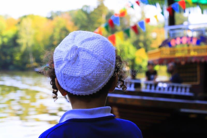 Der Junge hasidic Jude betrachtet das Vergnügensschiff im See in Uman, Ukraine, die Zeit des jüdischen neuen Jahres lizenzfreies stockfoto