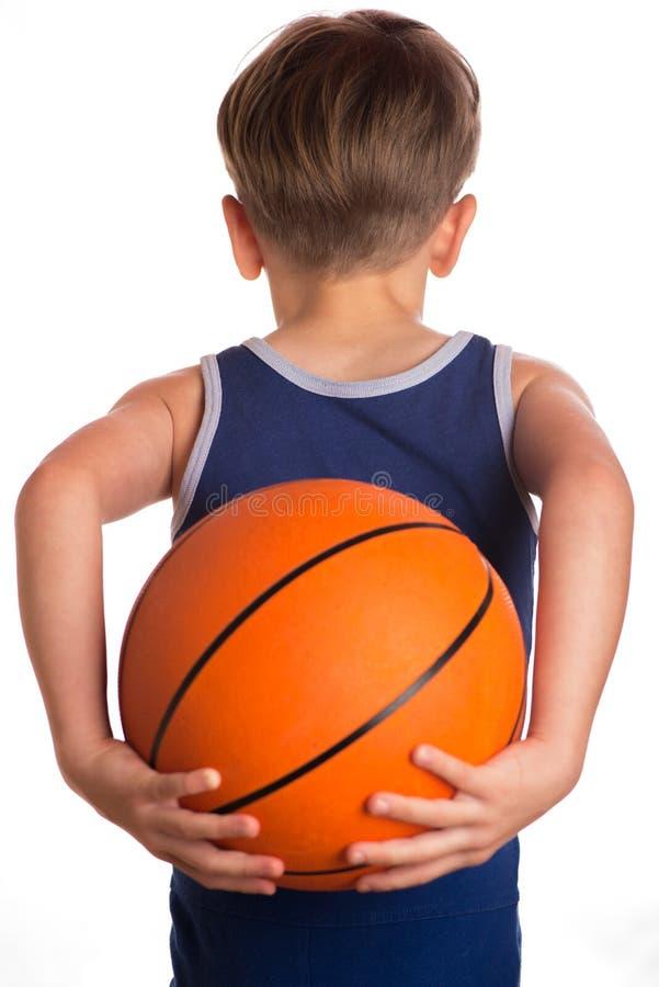Der Junge hielt einen Basketballball hinter der Rückseite lizenzfreie stockfotos