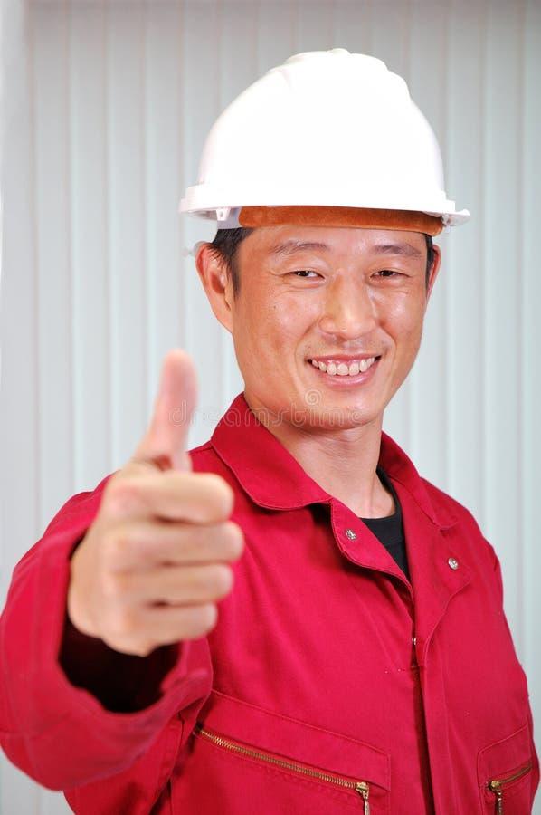 Der junge Ingenieur, die Arbeitskraft in der roten Uniform. stockbild