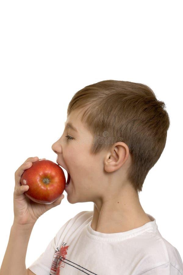 Der Junge isst einen Apfel stockfotografie