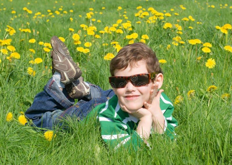 Der Junge ist auf dem Gras stockbilder