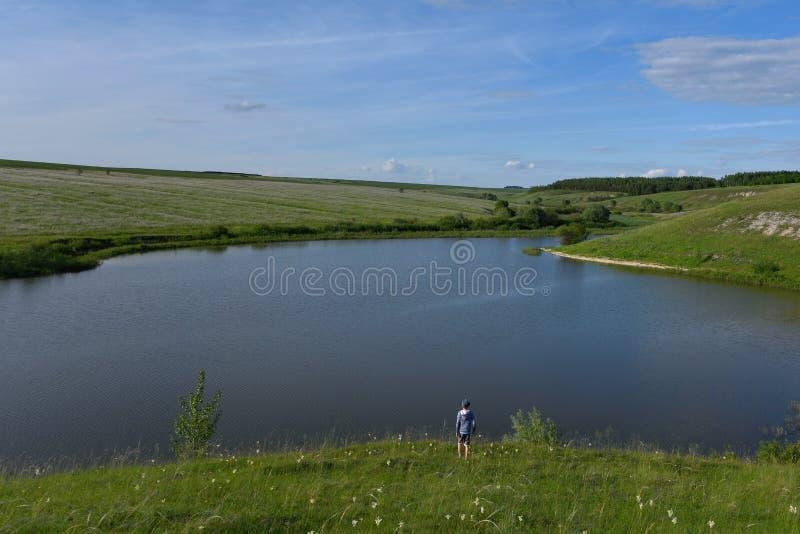 Der Junge ist froh und läuft zum Fluss stockfotografie