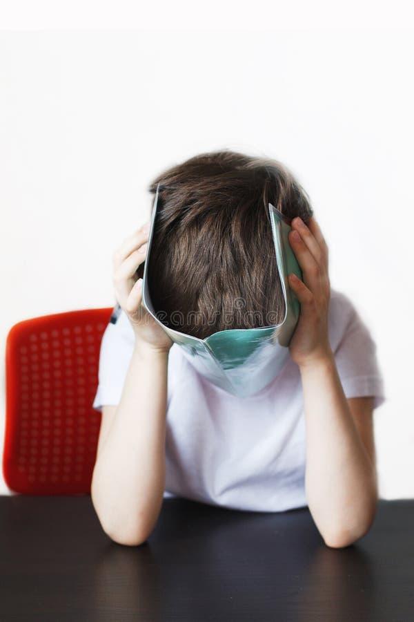Der Junge ist vom Handeln von Hausarbeit müde das Kind bedeckte Gesicht mit einem Notizbuch stockbilder
