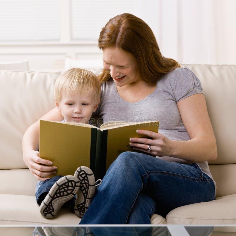 Der junge Junge, der auf Mutter hört, las ihn eine Geschichte stockfoto