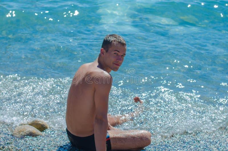 Der junge Kerl sitzt auf dem Strand glücklicher junger Mann, der Ferien auf Seestrand genießt lizenzfreie stockfotos