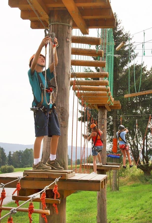 Der Junge klettert im Park des Abenteuers (Seil) stockfotografie