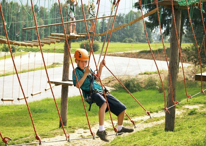 Der Junge klettert im Park des Abenteuers (Seil) stockbild